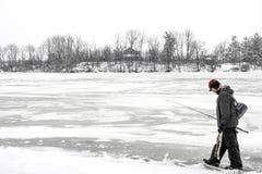 Pescatore all'aperto che cammina attraverso un lago congelato nel carryin di inverno fotografia stock