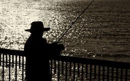 Pescatore Alone su un pilastro fotografia stock