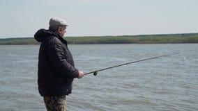 Pescatore anziano Angling su un fiume in primavera video d archivio