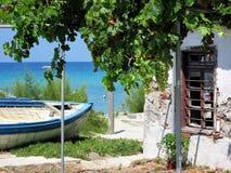 Pescatore anziano Boat su terra accanto alla casa abbandonata in Grecia, Chalkidiki immagini stock