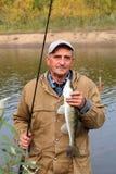 Pescatore anziano ed il suo fermo - zander fotografie stock libere da diritti