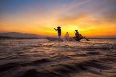 Pescatore asiatico della siluetta sulla barca di legno Fotografia Stock Libera da Diritti