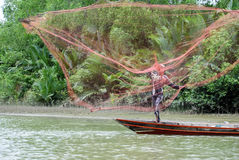 Pescatore asiatico sulla barca di legno Immagine Stock