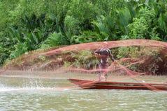Pescatore asiatico sulla barca di legno Fotografie Stock