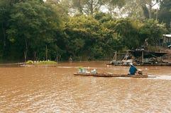 Pescatore asiatico sulla barca di legno del longtail nel fiume della natura fotografia stock libera da diritti