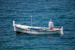 Pescatore in barca di legno tradizionale in mare fotografie stock