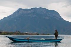 Pescatore in barca sul lago Lugu Immagine Stock Libera da Diritti