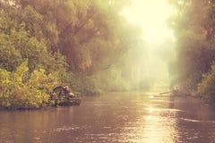 Pescatore in barche sul fiume nebbioso immagine stock