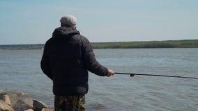 Pescatore Casting della mosca al pesce aumentante su un fiume archivi video