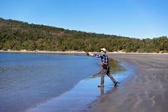 Pescatore Casting His Rod della spiaggia Immagini Stock Libere da Diritti