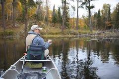 pescatore caucasico 40s che pesca sul piccolo lago nel Minnesota del Nord durante la caduta immagine stock