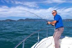 Pescatore che combatte grande pesce sull'oceano dalla barca immagine stock libera da diritti
