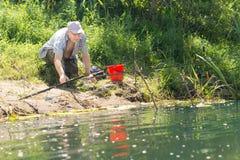 Pescatore che controlla canna da pesca fotografie stock