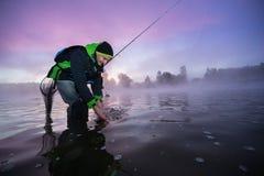 Pescatore che dà una libertà al piccolo pesce predatore immagine stock libera da diritti