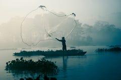 Pescatore che fonde fuori la sua rete da pesca nel fiume Immagine Stock