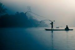 Pescatore che fonde fuori la sua rete da pesca nelle prime ore del mattino Fotografie Stock Libere da Diritti