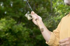 Pescatore che fonde una barretta con l'attrezzatura leggera Fotografia Stock Libera da Diritti
