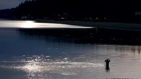 Pescatore che guada in un lago stock footage