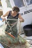 Pescatore che rimuove le reti del pesce fotografie stock libere da diritti