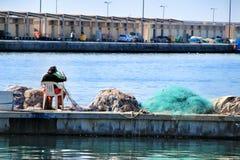 Pescatore che ripara le reti nel bacino di Santa Pola fotografie stock libere da diritti