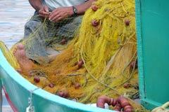 Pescatore che ripara rete da pesca in Panormitis Isola di Symi, Grecia Immagine Stock