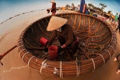 Pescatore che ripulisce il suo canestro di pesca sulla spiaggia Immagine Stock Libera da Diritti