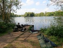 Pescatore che si inclina dal lato del lago a Rickmansworth Aquadrome immagini stock