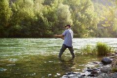 Pescatore che sta fiume vicino e che tiene canna da pesca fotografia stock libera da diritti