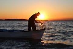 Pescatore che tiene l'ancora sulla barca e sul tramonto Fotografia Stock