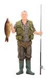 Pescatore che tiene un pesce e una canna da pesca Fotografie Stock