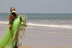 Pescatore che tira una rete da pesca Fotografie Stock Libere da Diritti