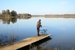 Pescatore con il baccello della barretta, alimentatori, allarmi elettronici del morso sul pilastro immagine stock