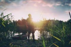 Pescatore con la canna da pesca sul lago fotografie stock