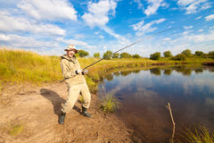 Pescatore con la pesce-barretta in sue mani che pescano vicino ad uno stagno Fotografia Stock Libera da Diritti