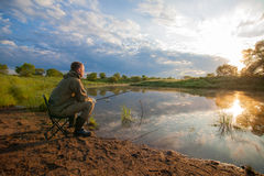 Pescatore con la pesce-barretta in sue mani vicino ad uno stagno Immagini Stock Libere da Diritti