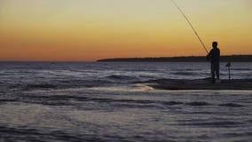 Pescatore con la siluetta di filatura al tramonto del mare video d archivio