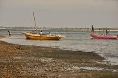 Pescatore con le barche alla riva Fotografia Stock