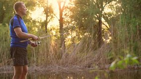 Pescatore con un pesce di cattura della barretta di filatura su un fiume stock footage