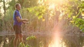 Pescatore con un pesce di cattura della barretta di filatura su un fiume archivi video