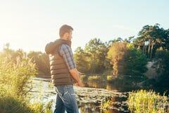 Pescatore con un pesce di cattura della barretta di filatura in un fiume Fotografia Stock Libera da Diritti