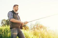 Pescatore con un pesce di cattura della barretta di filatura in un fiume Immagini Stock