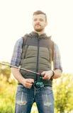 Pescatore con un pesce di cattura della barretta di filatura in un fiume Fotografie Stock