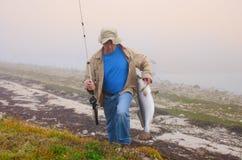 Pescatore con un pesce enorme su una mattina nebbiosa Fotografie Stock Libere da Diritti