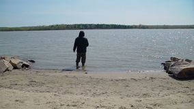 Pescatore con una canna da pesca su una sponda del fiume video d archivio