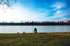 Pescatore con una canna da pesca sulla sponda del fiume gatti Cielo blu immagine stock libera da diritti