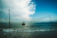 Pescatore con una maglia su una barca rotonda fuori dalla costa del Vietnam Fotografia Stock