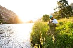 Pescatore della mosca sulla sponda del fiume ad alba Fotografie Stock