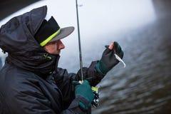 Pescatore di sport che mostra il pesce di plastica dell'esca fotografia stock libera da diritti
