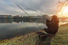 Pescatore di sport che prova a pescare pesce in fiume, pesca urbana immagine stock