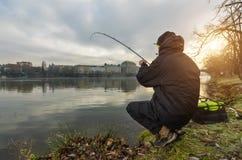 Pescatore di sport che prova a pescare pesce in fiume, pesca urbana fotografie stock